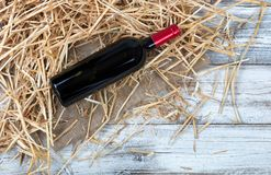 An unopen bottle of red wine on top of straw and burlap with whi Stock Photography