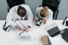 Overhead view of scientific researchers in white coats working together at workplace. In laboratory stock photo