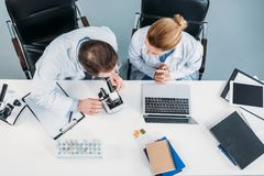 Overhead view of scientific researchers in white coats working together at workplace with microscope and laptop. In laboratory royalty free stock photography