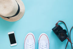 Overhead view selfie of feet in sneakers with smartphone, camera and hat. On pastel color floor Stock Photos