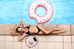 Overhead view of sexy young girl relaxing at poolside on summer day