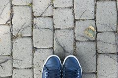 Overhead view of shoes on gray stone ground. Shoes on a stone background. Sneakers on a stone floor. Sport fitness shoes footwear. And objects concept Stock Photos