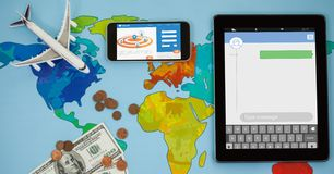 Overhead view of smart phone and tablet computer on world map with currency. Digital composite of Overhead view of smart phone and tablet computer on world map Stock Photos