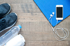 Overhead view of smartphone with earphone on blue yoga mat Royalty Free Stock Photos
