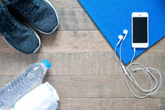 Overhead view of smartphone with earphone on blue yoga mat Stock Image
