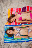 Overhead view of smiling attractive women tanning in the sun. Overhead view of young smiling women tanning in the sun on beach towels Royalty Free Stock Photo