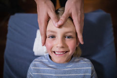Overhead view of smiling boy receiving head massage from female therapist royalty free stock photo