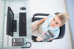 Overhead view of smiling businesswoman showing calculator Royalty Free Stock Images