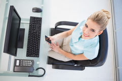 Overhead view of smiling businesswoman text messaging Stock Photo