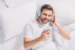 Overhead view of smiling man. In headphones using smartphone in bed stock photo