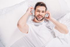 Overhead view of smiling man. Listening music in headphones while resting in bed royalty free stock images
