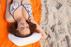 Overhead view of a smiling young woman lying on her beach towel Stock Photo