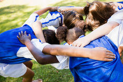 Overhead view of soccer team forming huddle Stock Photos