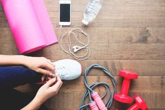 Overhead view of sport and fitness woman tying shoes with mobile devices and sport equipments on wooden stock photos