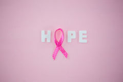 Overhead view of spotted Breast Cancer Awareness ribbon with HOPE text Stock Photos
