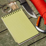 Overhead view of survival gear equipment to survive and Notebook royalty free stock images
