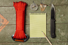 Overhead view of survival gear equipment to survive and Notebook. With Pen. Items include knife, red rope, notepad, pen, compass, matches. Writing Notes for royalty free stock photos