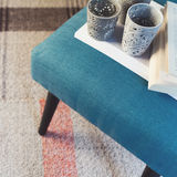 Overhead view of teal ottoman and votive candle holders. On striped rug stock photo