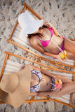 Overhead view of teenage girls sitting on deck chairs Royalty Free Stock Photo