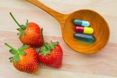 Vitamins and strawberries. Overhead view of three different medicine capsules of vitamins in a wooden spoon beside three strawberries, on a light wood table Stock Images
