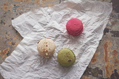 Overhead view of three yummy macaroons on crumpled paper. Rustic background Stock Photos