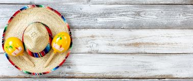 Flat lay view of traditional Cinco De Mayo objects on white weathered wooden boards. Overhead view of traditional maracas on top of a large sombrero for Cinco de stock photography