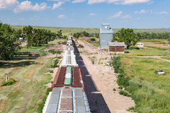 Overhead View of Train Passing Old Grain Elevator Royalty Free Stock Images