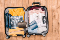 Overhead view of traveler`s accessories organized in open luggage Stock Photos