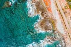 Overhead view of turquoise sea, waves and a rocky shoreline.  stock photography