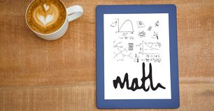 Overhead view of various math equations in digital tablet by coffee cup at table royalty free stock photography