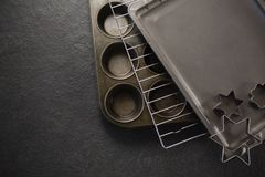 Overhead view of various pastry cutter and baking sheet with cooling rack on muffin tin. At table Royalty Free Stock Photo
