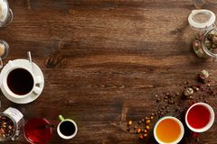 Various sorts of tea and coffee with copyspace. Overhead view of various sorts of tea and coffee. Flavoured with Assorted Herbs and coffee beans on a rustic wood royalty free stock image