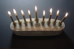 Overhead view of a white and gold Hanukkah menorah with candles lighted. Horizontal aspect, space for text Stock Photography