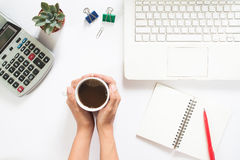 Overhead view of woman hand holding cup of coffee with laptop Stock Photography