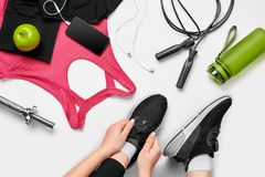 Overhead view of woman hands tying shoes with sport equipments on white background royalty free stock images