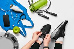 Overhead view of woman hands tying shoes with sport equipments on white background stock photo
