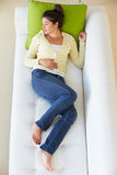 Overhead View Of Woman Relaxing On Sofa royalty free stock image