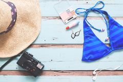 Overhead view of Woman`s essentials summer vacation concept on v. Intage blue wooden background Royalty Free Stock Photo