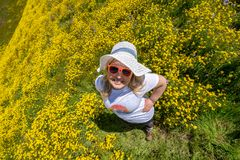 Overhead view of a woman in a yellow wildflower field wearing hiking clothing and a straw sun hat. Concept for seasonal allergies.  royalty free stock photography