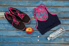 Overhead view of womenswear with apple and bottle by headphones. On wooden table Royalty Free Stock Images