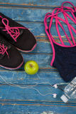 Overhead view of womenswear with Granny Smith apple and bottle by headphones. On wooden table Stock Photo
