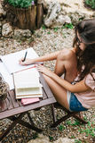 Overhead view of young beautiful female sitting outside and studying hard. Royalty Free Stock Photo