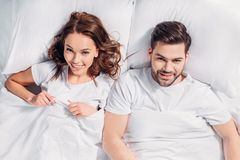 overhead view of young cheerful couple in love looking at camera while lying royalty free stock image