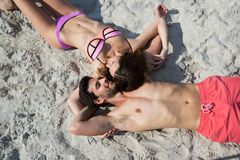Overhead view of young couple lying together on sand at beach Royalty Free Stock Photography