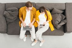 overhead view of young couple using digital devices on cozy couch stock photos