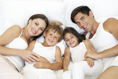 Overhead View Of Young Family Lying In Bed Stock Photography