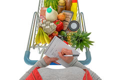 Overhead woman checking shopping list isolated. Overhead photo of a woman checking her shopping list with a trolley full of fresh food, isolated on a white Royalty Free Stock Photography