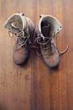 Overhead of worn old work boots on wooden floor Stock Photo