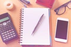 Overheadkosten van bureaulijst met notitieboekje, pen, mobiele telefoon, calc Royalty-vrije Stock Foto's