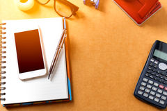 Overheadkosten van bureaulijst met notitieboekje, pen, mobiele telefoon, calc Stock Afbeeldingen